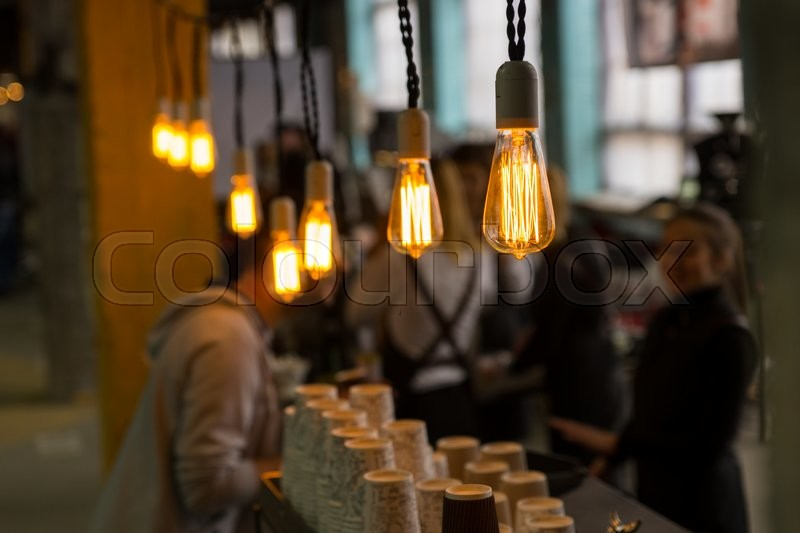 lightbulbs bare. selective focus view on bright yellow filaments inside bare light bulbs in crowded cafe with cups counter | stock photo colourbox lightbulbs l