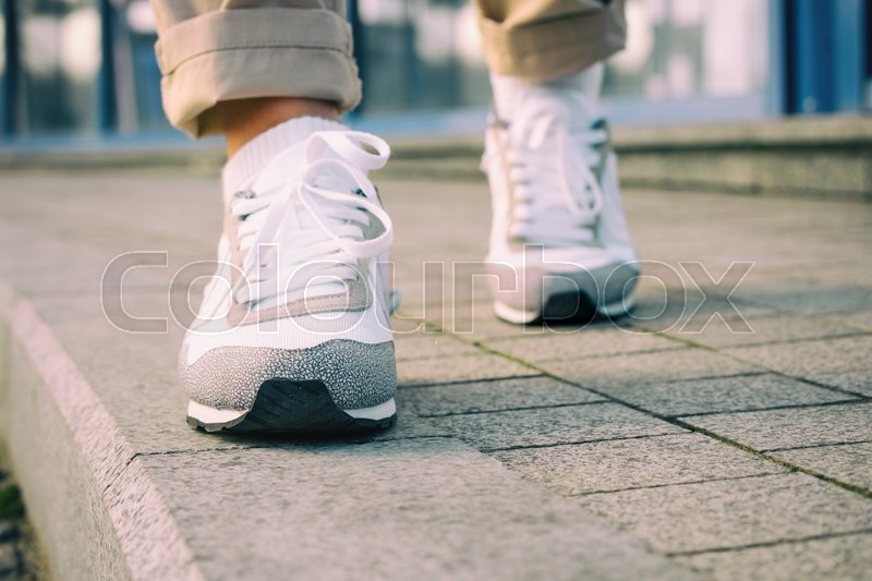 Female feet in white sneakers walking on the sidewalk, low angle, retro colors, stock photo