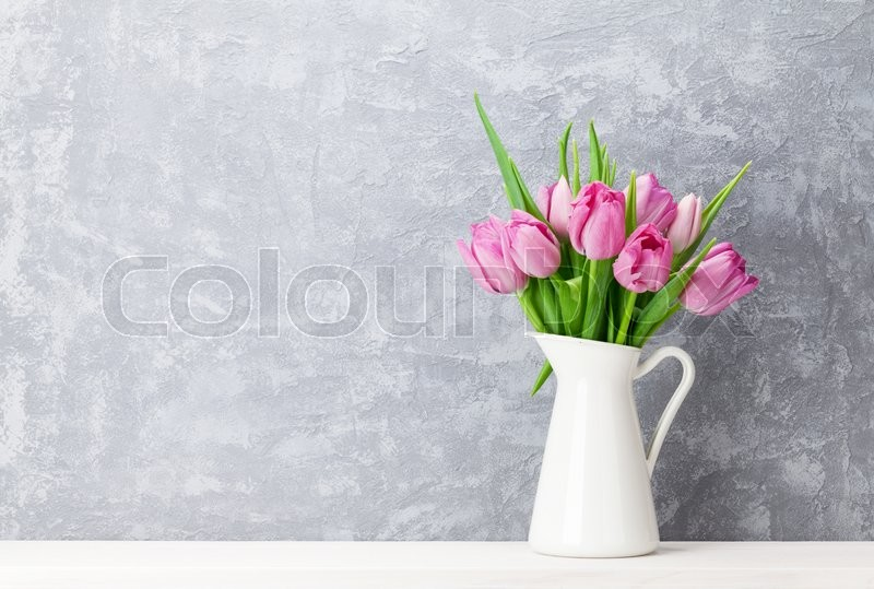 Fresh pink tulip flowers bouquet on shelf in front of stone wall. View with copy space, stock photo