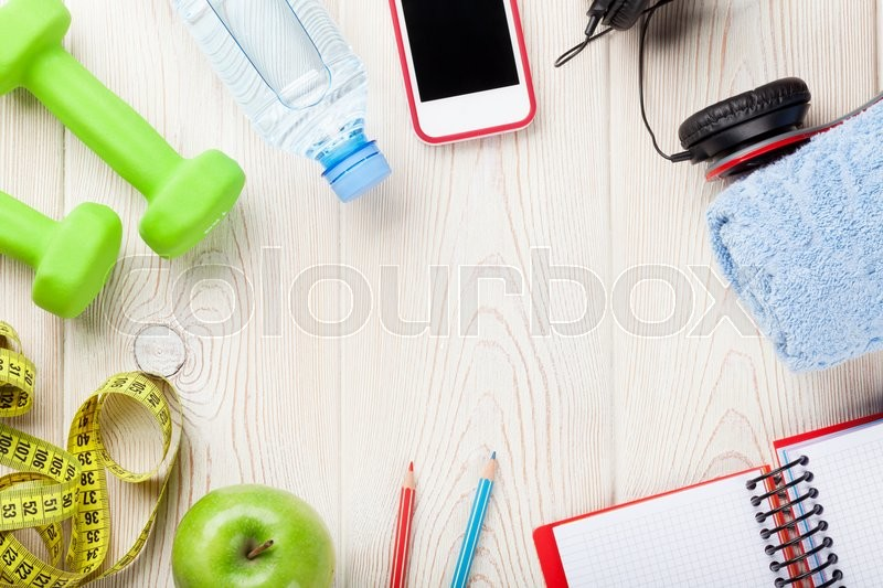 Health and fitness concept. Dumbbells, water bottle, smartphone, headphones and notepad. Top view with copy space, stock photo