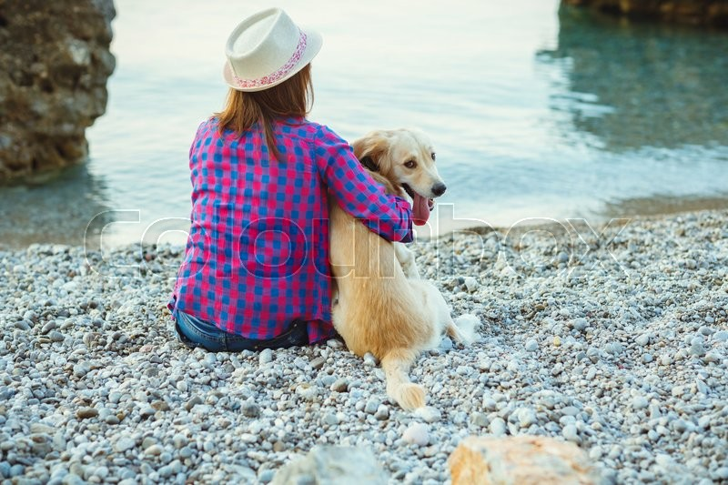 Summer vacation - woman with a dog on a walk on the beach, stock photo