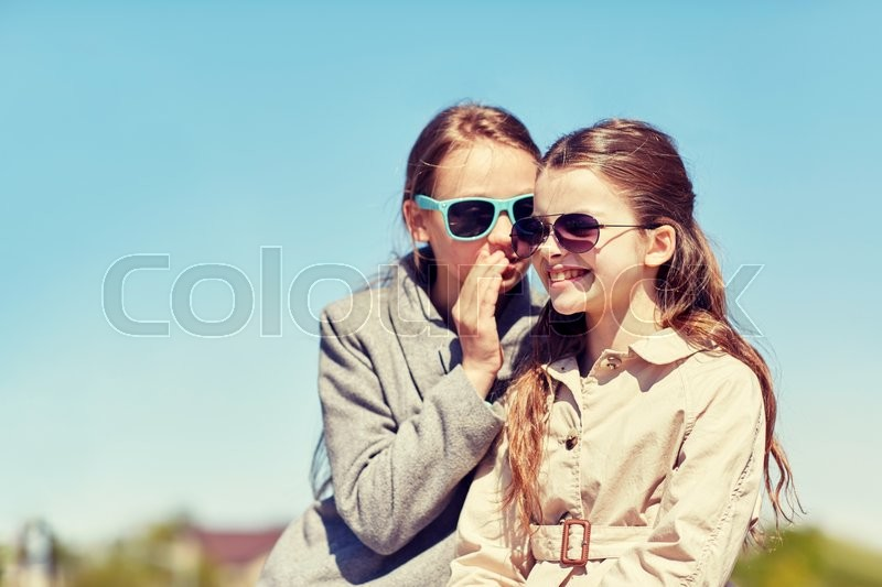 People, children and friendship concept - happy little girl in sunglasses whispering her secret to friends ear or gossiping outdoors, stock photo
