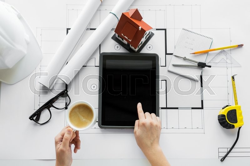 Business, architecture, building, construction and people concept - close up of architect hand with living house blueprint and tablet pc computer, stock photo