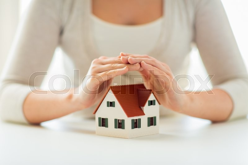 Architecture, safety, security, real estate and property concept - close up of hands protecting house or home model, stock photo
