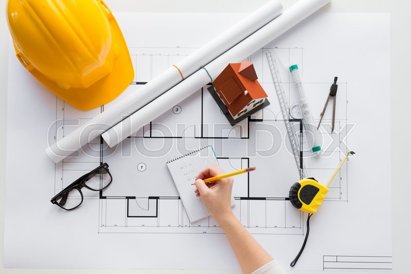 Business, architecture, building, construction and people concept - close up of architect hand with blueprint and architectural tools writing to notebook, stock photo