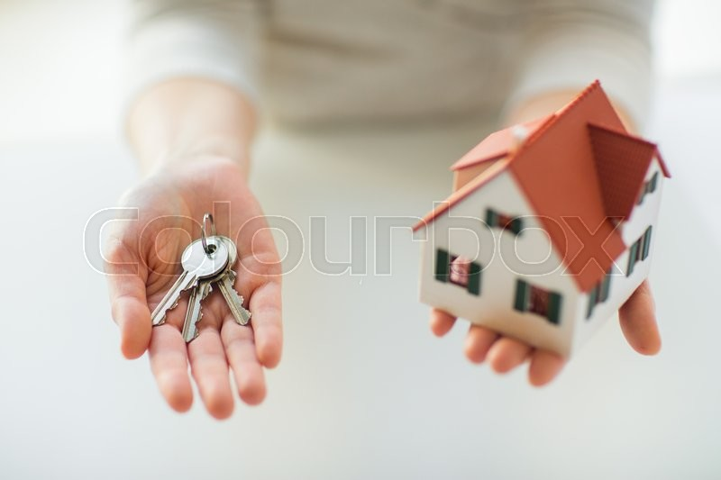 Building, mortgage, real estate and property concept - close up of hands holding house model and home keys, stock photo