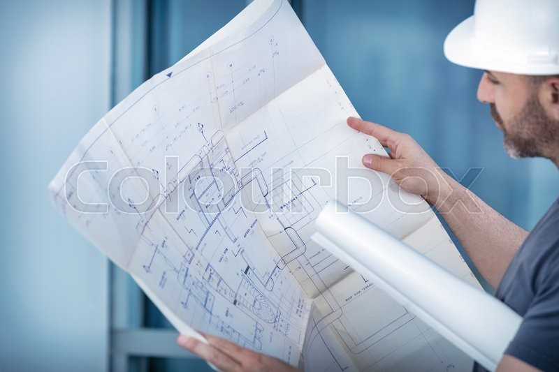 Portrait of an architect builder studying layout plan of the rooms, serious civil engineer working with documents on construction site, building and home renovation, professional foreman at work , stock photo