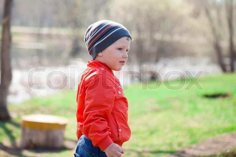 61f343fe8 Baby boy in orange jaket and blue jeans