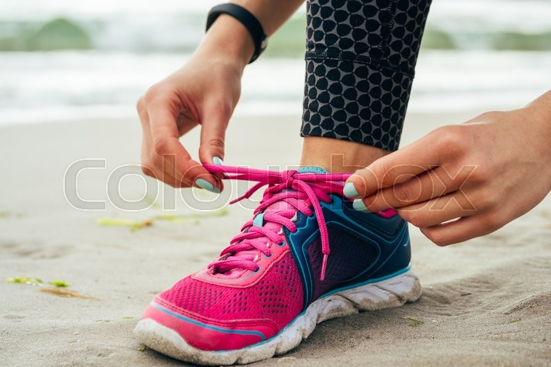 Female hands with manicure tie laces on pink and blue sneakers on the beach close up, stock photo
