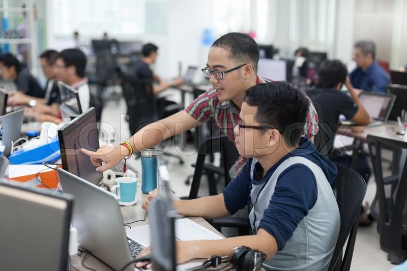 Asian Colleagues Software Developers Team Sitting At Desk Working Laptop Computer Business People Group Real Office, stock photo