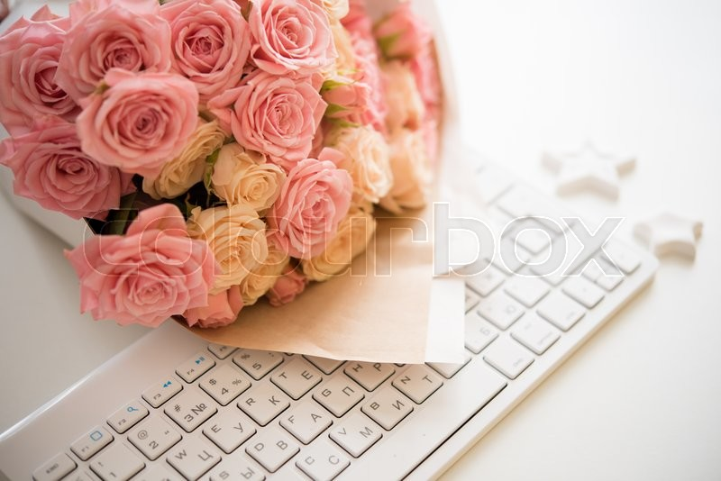 Bouquet of pink and beige roses on white computer keyboard, modern workplace closeup, stock photo