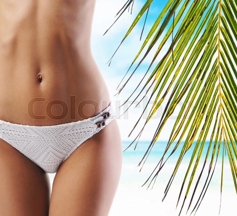 Close-up of beautiful female body. Sporty woman with a perfect body relaxing on beach at summer. Sea and sky background. , stock photo