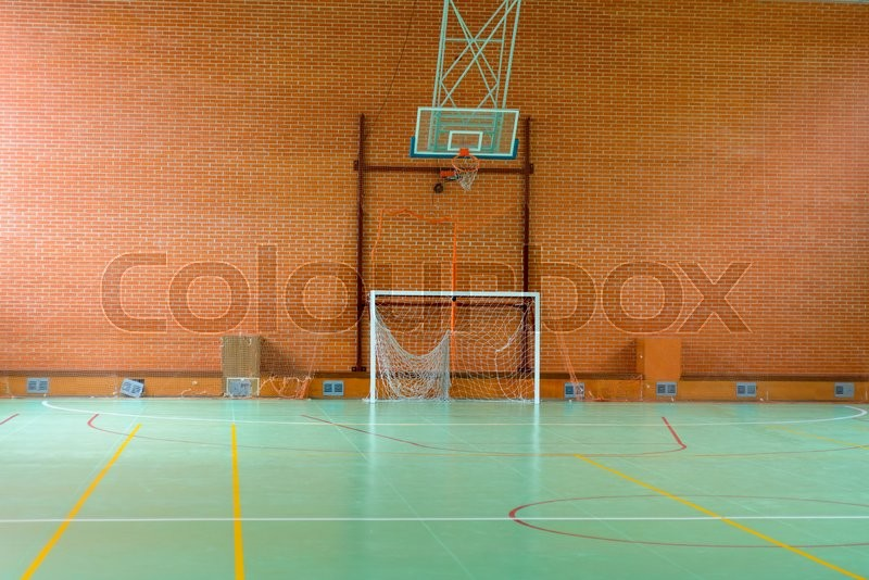 View across in indoor sports court with goalposts and a basketball hoop and net against a red brick wall, empty background view, stock photo
