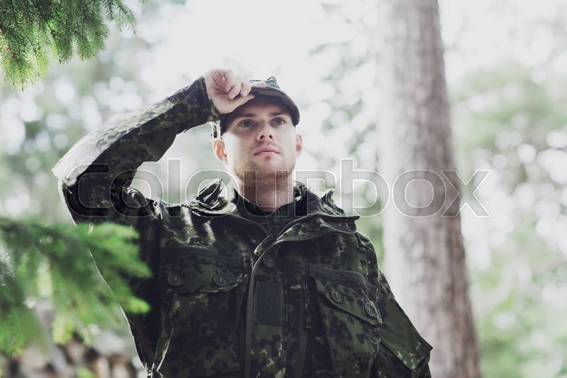 War, army and people concept - young soldier or ranger wearing military uniform in forest, stock photo