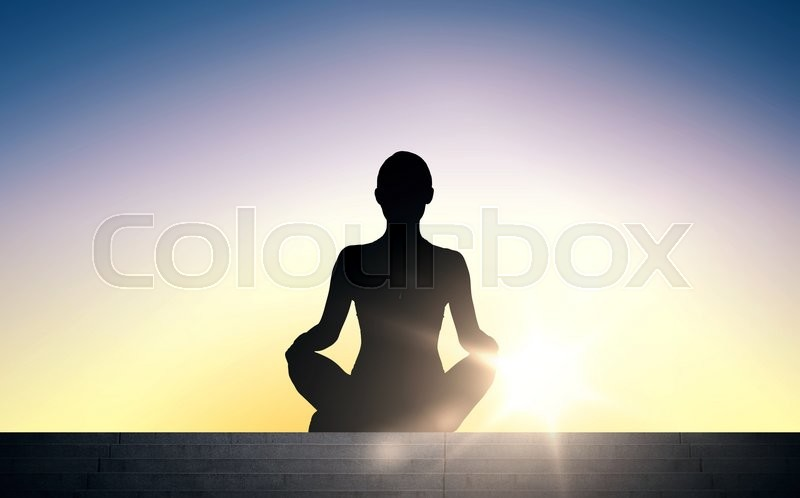 People, health, wellness and meditation concept - woman meditating in yoga lotus pose on stairs over sun light background, stock photo