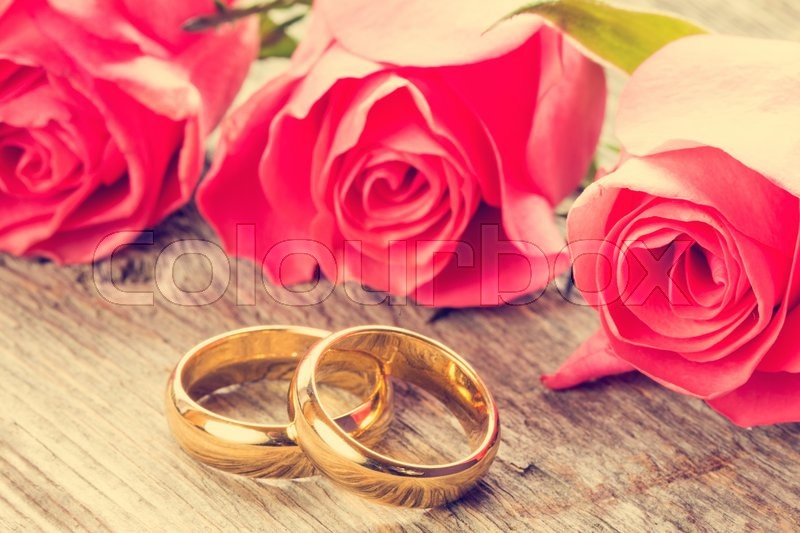 Wedding Rings With Pink Roses On Wooden Stock Photo