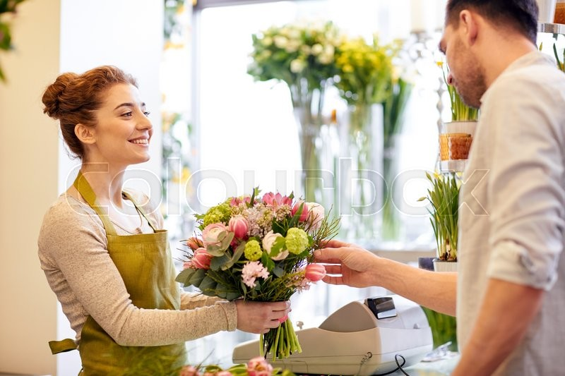 People, shopping, sale, floristry and consumerism concept - happy smiling florist woman making bouquet for and man or customer at flower shop, stock photo