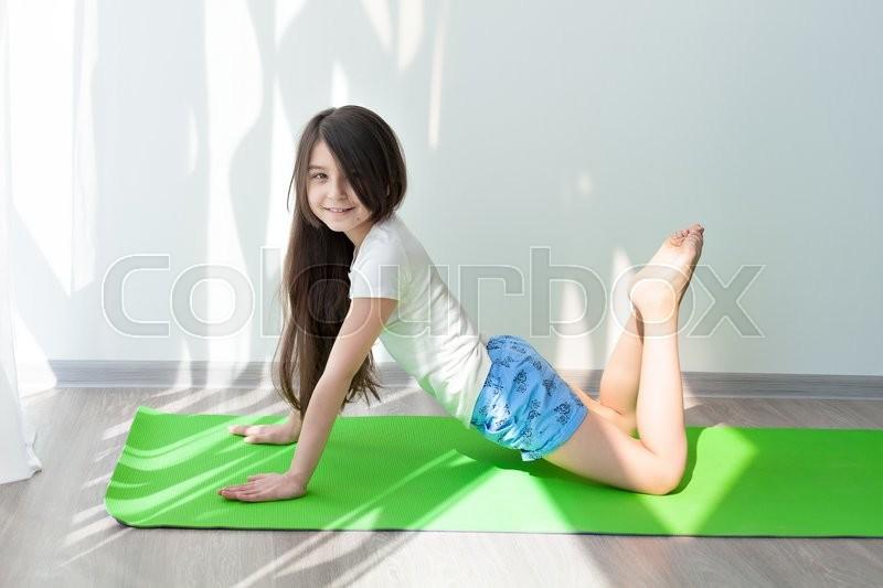 Little Girl Doing Gymnastics On A Green Yoga Mat Children