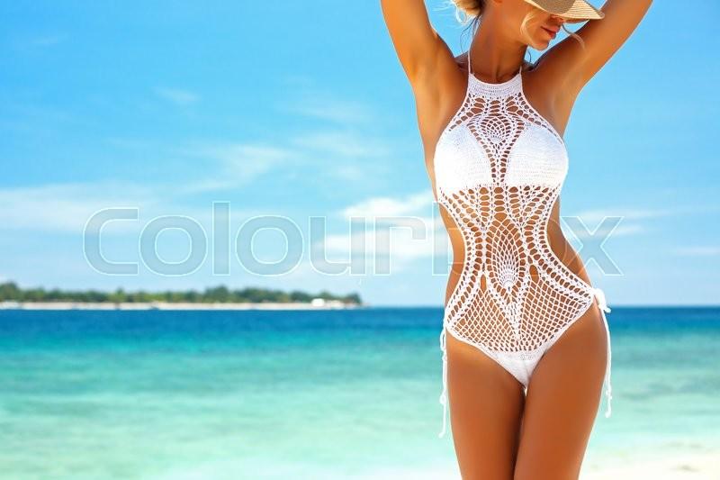 Beautiful woman wearing crochet bikini posing over the sea view, beach lifestyle, stock photo