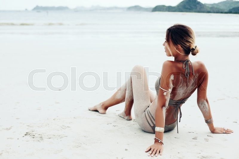 Beautiful bohemian styled and tanned girl at the beach, stock photo