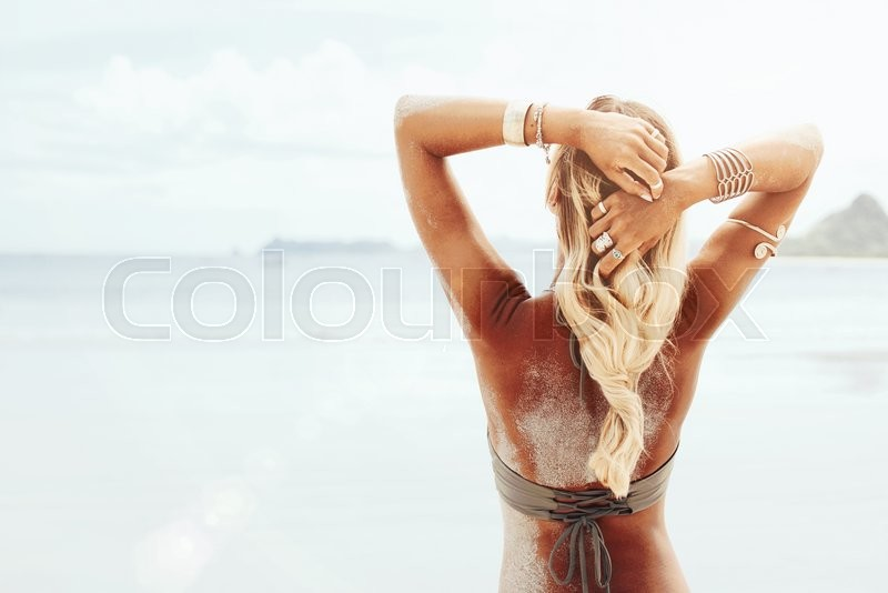 Beautiful bohemian styled and tanned girl at the beach in sunlight, stock photo