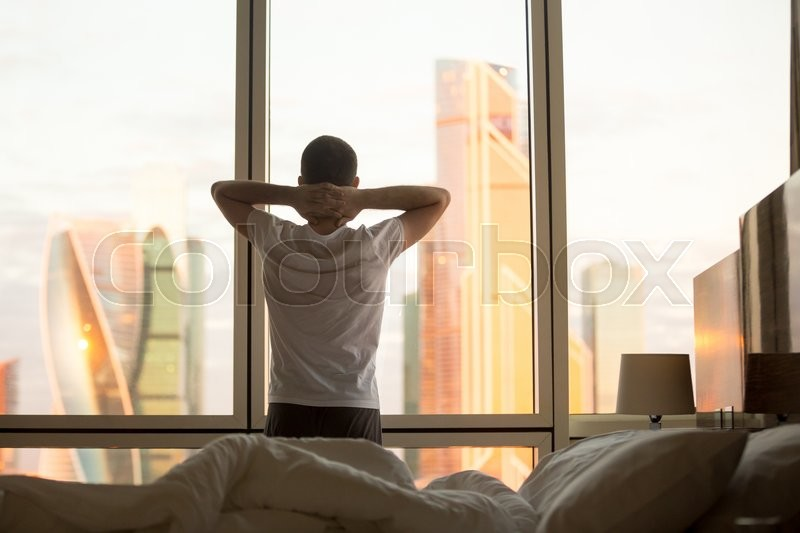 Rear view of young man looking at dawn city scenery in window after waking up. Handsome casual guy relaxing in the morning with hands crossed behind his head, stock photo
