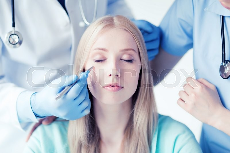 Healthcare, medical and plastic surgery concept - plastic surgeon and nurse with patient in hospital, stock photo