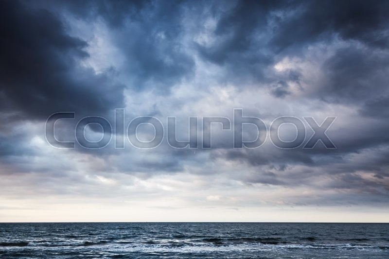 Dramatic stormy dark cloudy sky over sea, natural photo background, stock photo