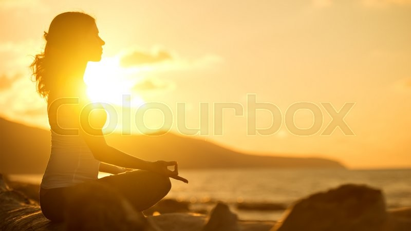 Yoga in the beach. woman meditating in lotus pose on the beach at sunset, stock photo