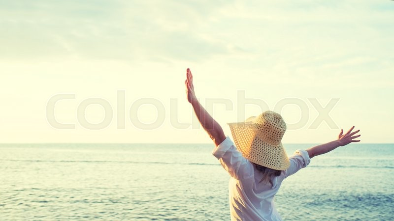 Happy woman standing arms outstretched back and enjoy life on the beach at Sea, stock photo