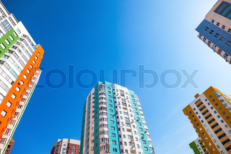 New tall apartment buildings against blue sky background, stock photo