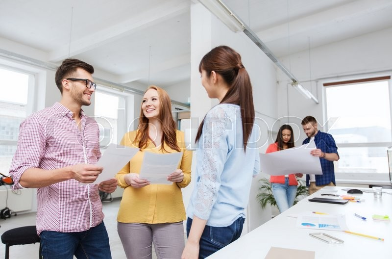 Business, communication, startup and people concept - happy multiracial creative team or students on coffee break talking at office, stock photo