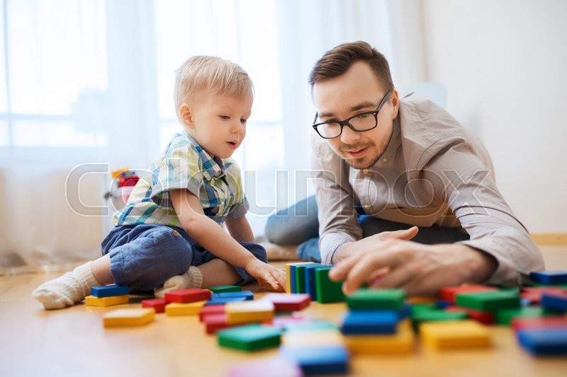 Family, childhood, creativity, activity and people concept - happy father and little son playing with toy blocks at home, stock photo
