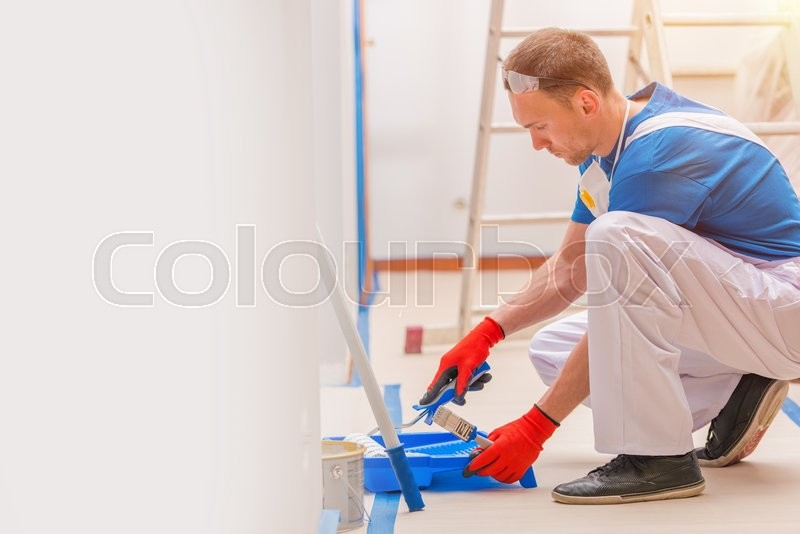 House Walls Painting. Young Caucasian Men Painting His Home. Construction and Renovation, stock photo