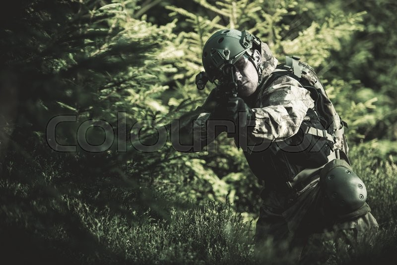 Special Forces Soldier. Camouflaged Marine Soldier Shooting Assault Rifle. Army Military Mission Concept Photo, stock photo