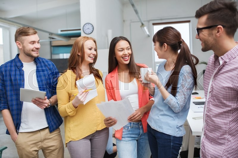 Business, communication, startup and people concept - happy international creative team or students on coffee break talking at office, stock photo