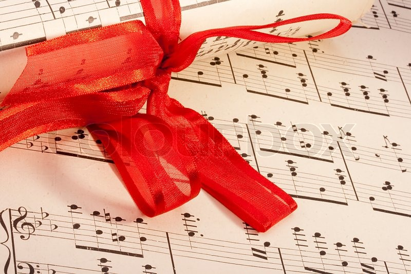 Theme music, old musical notes with roll bandaged red ribbon, stock photo
