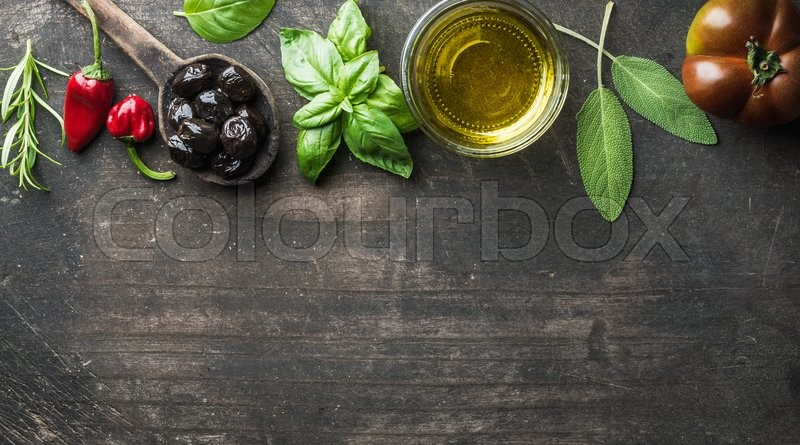 Food background with vegetables, herbs and condiment. Greek black olives, fresh basil, sage, rosemary, tomato, peppers, oil on dark rustic wooden background. Top view, copy space, stock photo
