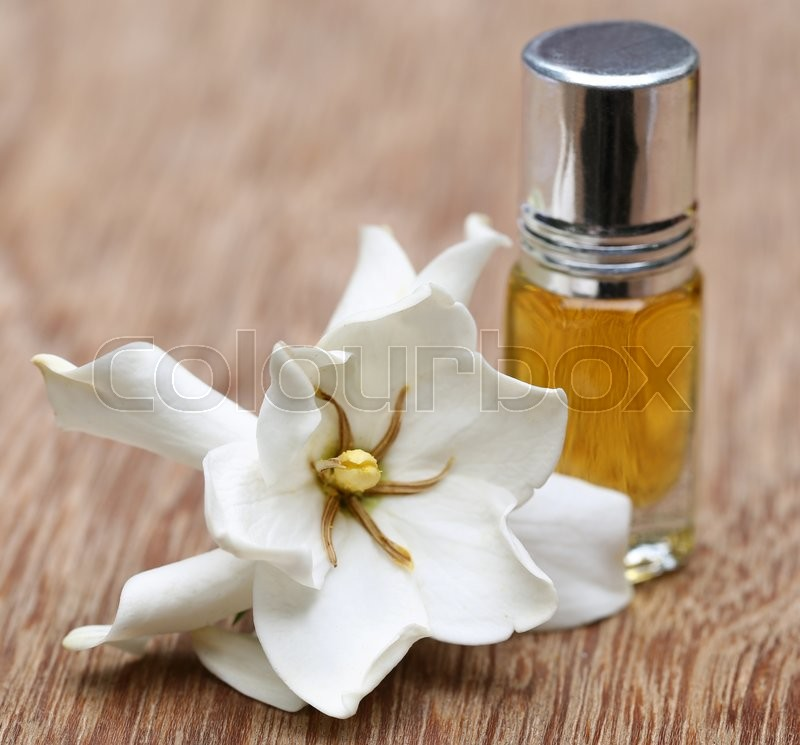 Gardenia or Gondhoraj flower with essence bottle on wooden surface, stock photo
