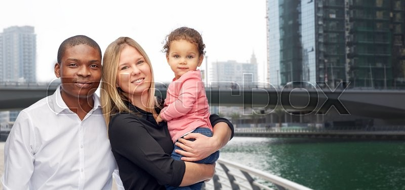 Family, travel, tourism and international concept - happy multiracial mother, father and little child over dubai city street background, stock photo