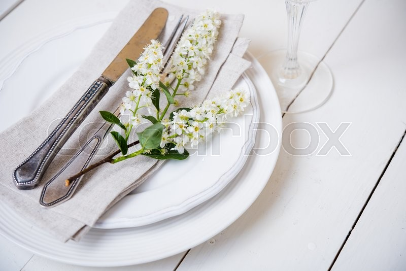 The snow white wedding table decor with bird cherry blossoms and cutlery, vintage rustic wedding table setting, stock photo