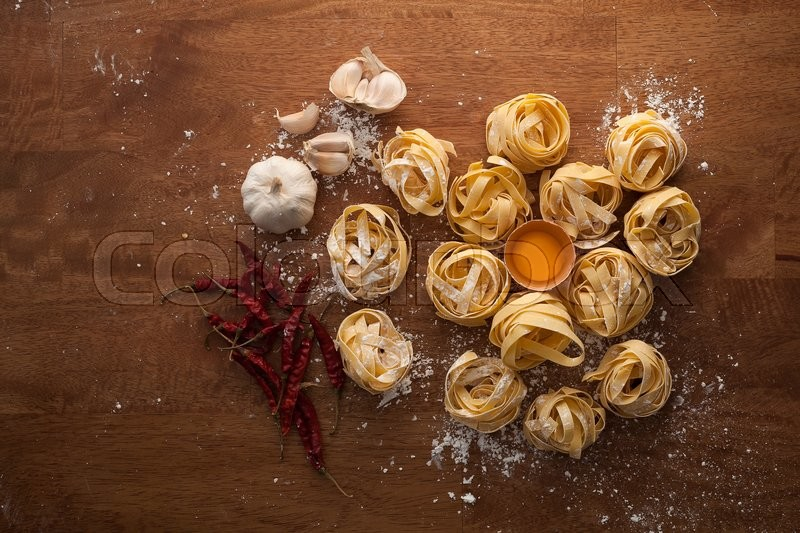 Stock foto af 'fettuccine pasta italian food still life rustic flat lay wood background tagliatelle alfredo garlic chili pepper