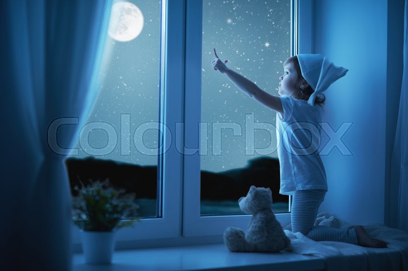 Child little girl at the window dreaming and admiring the starry sky at bedtime night, stock photo