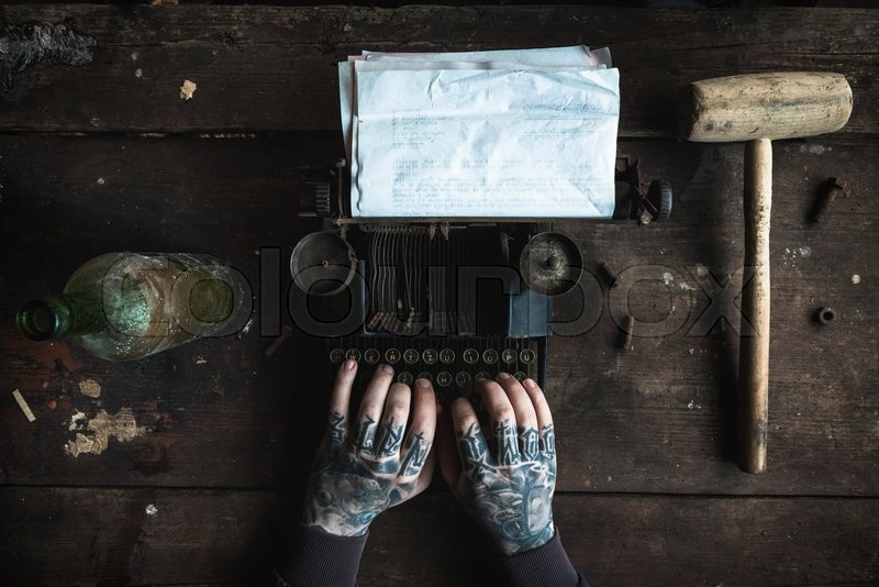 Writer with tattooed hand writing on old typing machine with blank paper,selective focus , stock photo