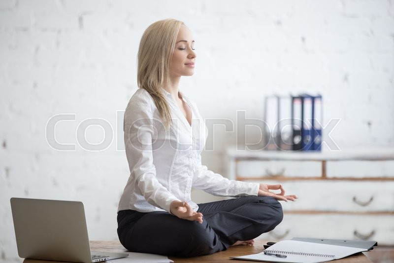 Business and healthy lifestyle concept. Portrait of young office woman sitting cross-legged in half lotus yoga pose at workplace. Smiling business lady meditating after finishing her work, stock photo