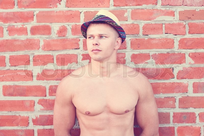 Handsome guy inflated athlete bodybuilder outdoors enjoying summer vacation resting shirtless, stock photo