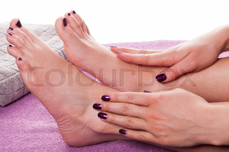 Manicured hands stroke bare feet painted with dark nail polish by ...