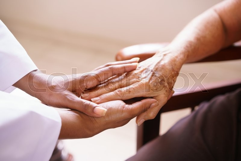 Old people in geriatric hospice: Aged patient receives the visit of a female black doctor. They shake their hands and talk in the hospital, stock photo