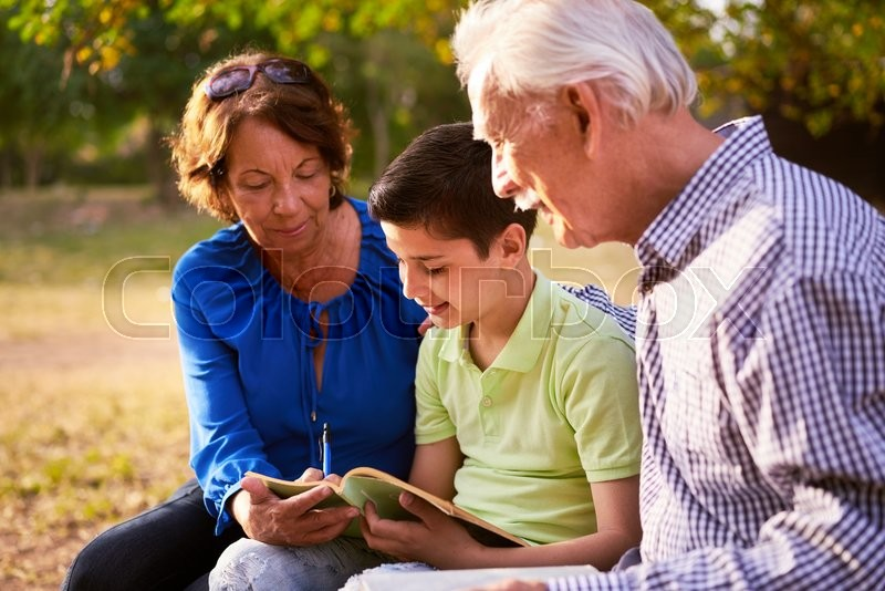 Grandparents educating grandson: Senior woman and old man spending time with their grandchild in park. The old people help the preteen kid studying and doing his school homework, stock photo