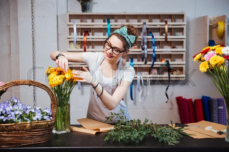 Smiling charming young woman florist taking care of yellow roses in flower shop, stock photo